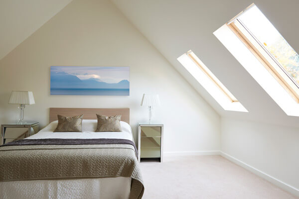 Bedroom interior showing landscape picture hanging above the bed