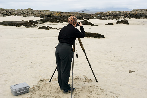 Jacky taking a landscape photograph on a beach in Scotland