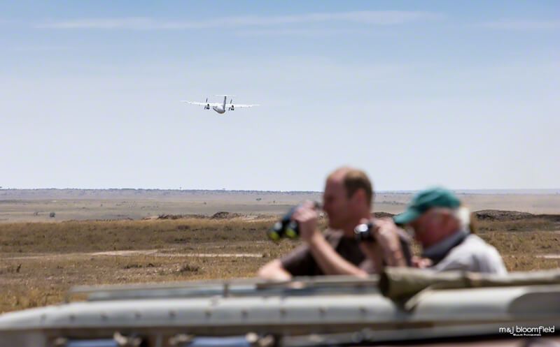 Tourists in a four by four safari vehicle watching game from the sunroof while a plane takes off from a bush air-strip in Kenya's Masai Mara